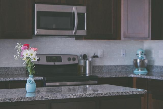 Płytki granitowe na blacie, z tyłu brązowe meble kuchenne